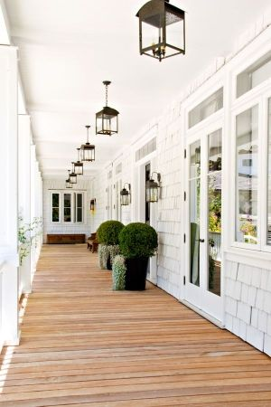 Loving the contrast of white siding, dark lanterns, highly ornamental greenery and worn wood of the deck.