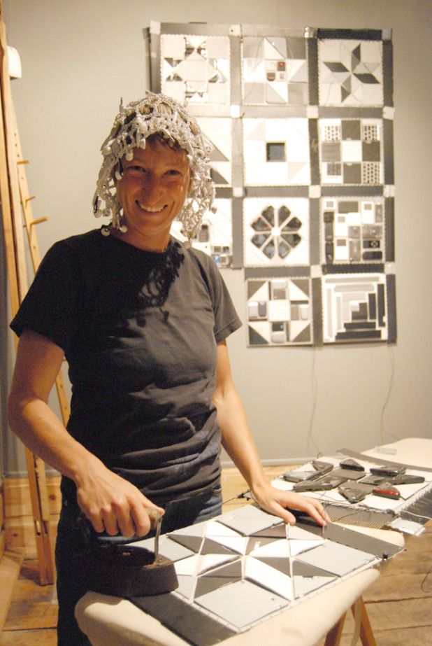 "Artist Elinor Whidden pretends to iron one of her ""quilt"" squares made of old computer parts. On her head is a bonnet made of earbuds and cables. Her exhibition at Rails End Gallery in Haliburton is about mixing the past and present and examining the work we do by hand. It is on until Oct. 11, 2015. JENN WATT Staff"