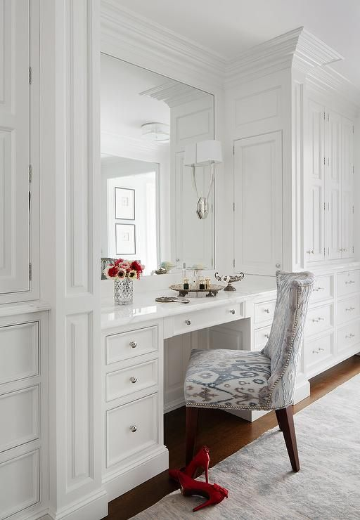 Gorgeous dressing room features a white built in make up vanity topped with white marble under a framed mirror illuminated by Ruhlmann Single Sconces alongside a blue and grey ikat chair.