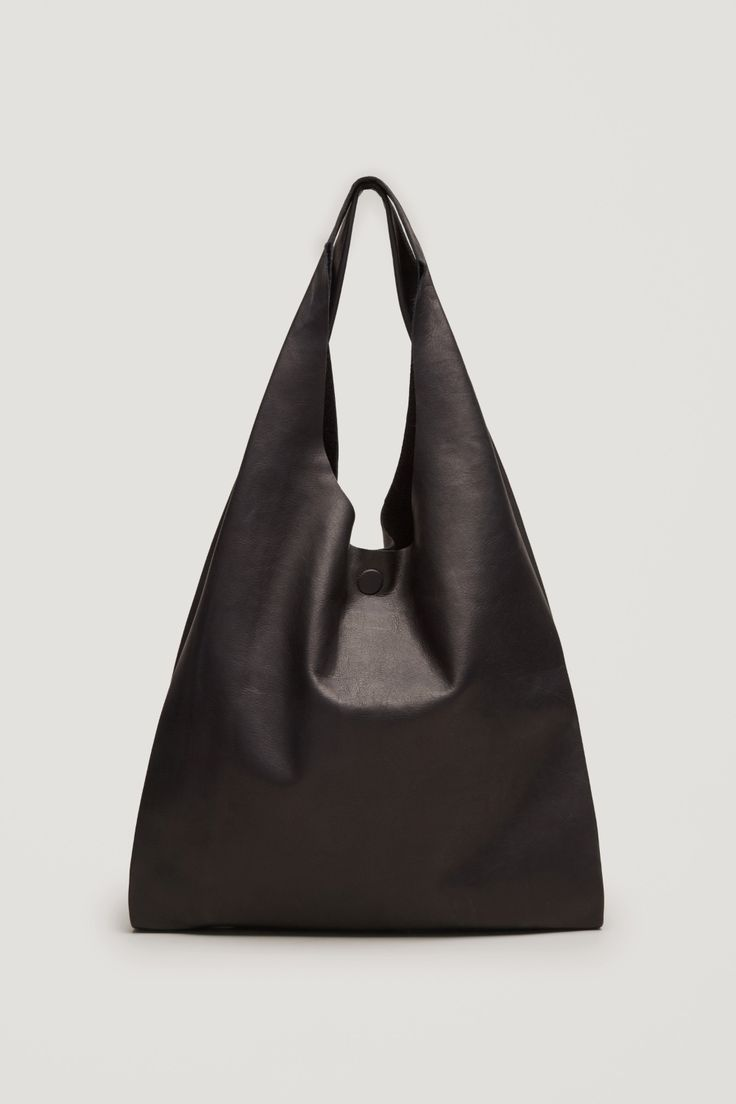 Made from soft leather with a subtle grained finish, this large leather has a single unlined compartment and a magnetic button fastening. A casual style, it can be held by the handles or worn over the shoulder.