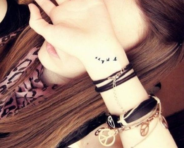 Tiny Birds Tattoo. Cute on the wrist.  I always see birds around the shoulder area.