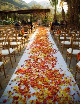 rust, yellow and orange rose petals against an ivory cloth runner FavorsUnlimitedFallinLove
