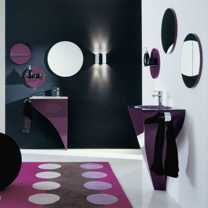 White and black stain wall feature round frameless wall mirror frame and round purple stain wooden wall unit with transparent glass floating shelf and white porcelain floor along with round geometric pattern purple fabric area rug also purple stain wooden bathroom vanities.