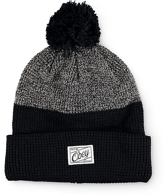 From the streets to the slopes, keep warm in premium fashion with this pom beanie made with a grey and black colorblock knit design finished with a brand tag at the cuff.