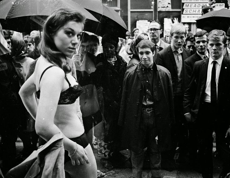 Men watch as a model takes part in a photo shoot in the window of a new Henry Moss boutique on London's fashionable Carnaby Street. May 11 1966