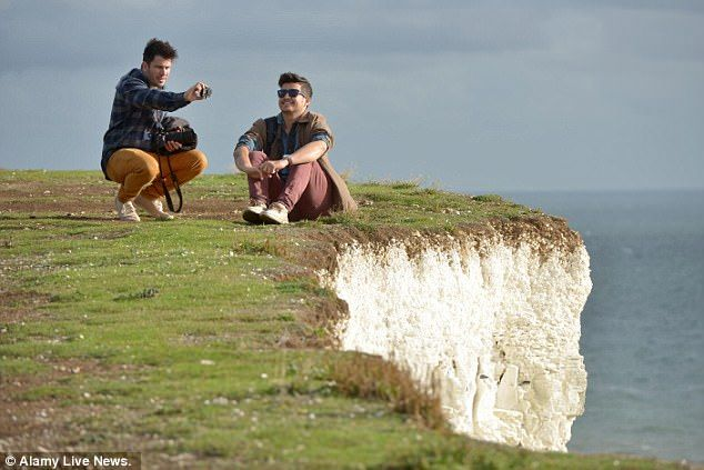 Dicing with death: Shocking photos show thrill seekers standing dangerously close to the crumbling cliff edge at Birling Gap, East Sussex