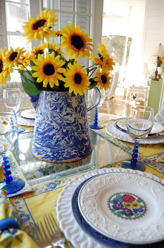 sunflowers with the blue pitcher for a lovely centerpiece...pretty placemats, and tinted stemware...