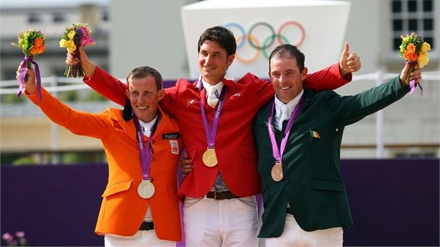 Steve Guerdat of Switzerland celebrates on the podium after winning the Gold medal, Gerco Schroder of Netherlands (L) the Silver medal and Cian O'Connor of Ireland (R) the Bronze medal in the Individual Jumping Equestrian on Day 12 of the London 2012 Olympic Games.