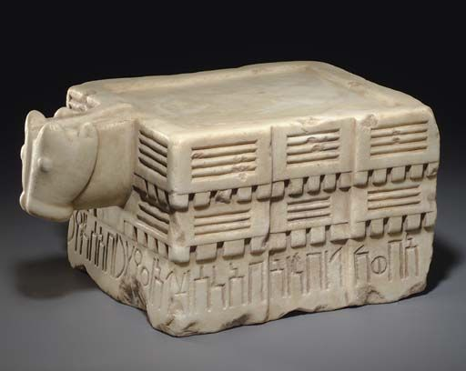 "South Arabian calcite libation table, 7th-6th century B.C. Rectangular table sculpted on three sides in three horizontal registers,  bottom register with an inscription reading  (Rt) 'b-wkl/bn/'b-'ns/s (Fnt) l'/c ttr/b'sn/yr (Lft) 'b/b-ywm/Smh-'mr, ""Ab-wakil, the son of Ab-anas, dedicated (this item) to 'Athtar Ba'san (=the Brave??), (when) he  an agreement/contract, in thetime of Sumhu-amir,""  one side with bull head, 38.9 cm long. Private collection"