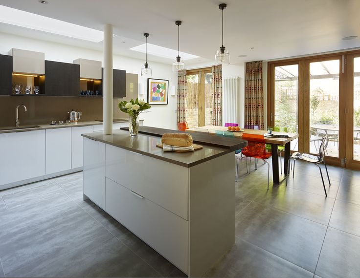 This modern open plan kitchen featuring Miele appliances and designed by Connaught Kitchens uses a compact breakfast bar as a stand alone island to break up the space and create interest #kitcheninspiration