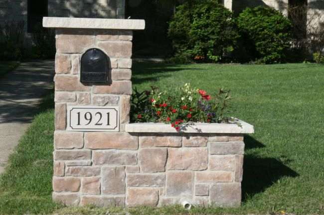 Stone mailbox in cobble stone and the color of Northern Brown Stone. Side planter for flowers is changed through the year for interest. Limestone caps and address stone.  www.northstarstone.biz  ca;; 847-996-6850