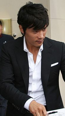 lee in a white shirt, black suit and pocket square. power dressing