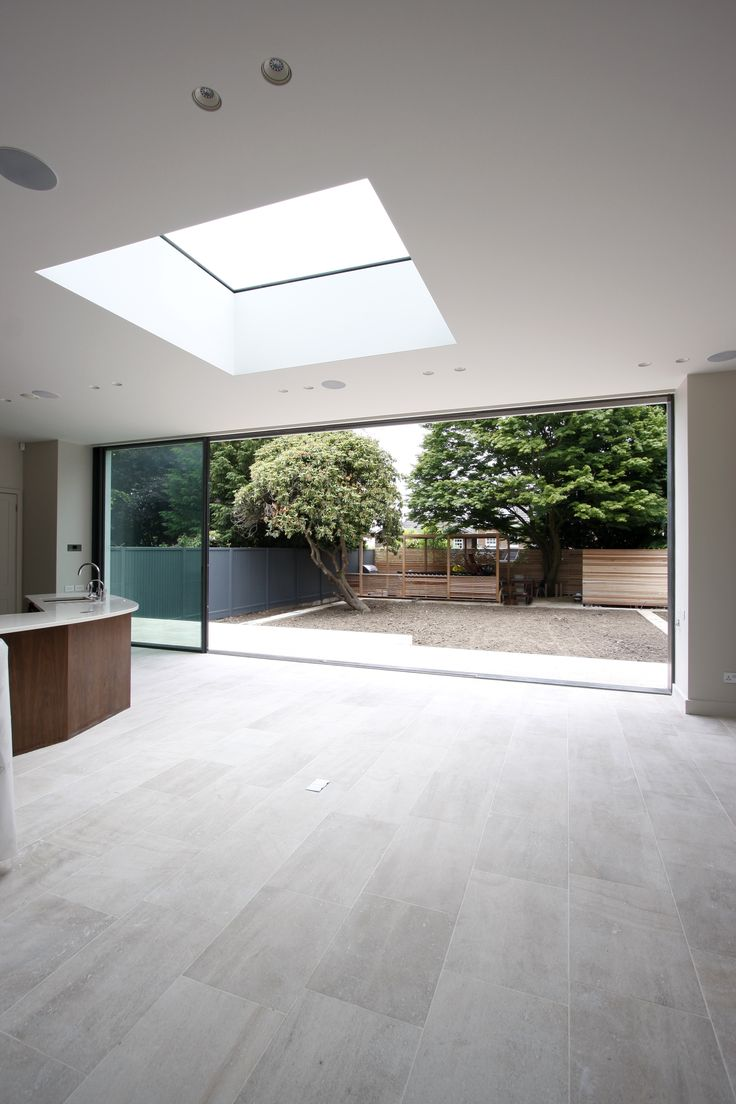 minimal windows slid open on rear extension with fixed, frameless rooflight above www.iqglassuk.com
