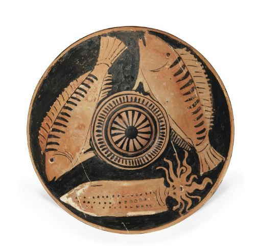 Apulian red-figured fish plate, attribuited to the Black and White stripe painter, 4th  century B.C.  With two striped perch and a squid around a central recess, down-turned rim with band of wave, details in added black, white and red, 23.5 cm diameter. Private collection