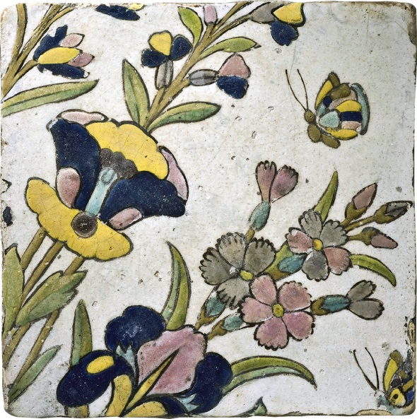BUTTERFLIES AND FLORAL SPRAYS - Iran (Safavid), 17th century - A tile in the cuerda seca technique in delicate shades of green, yellow, ochre, rose pink, greyish blue and black on a white ground, with an elegant design of a butterfly hovering over luxuriant floral sprays.