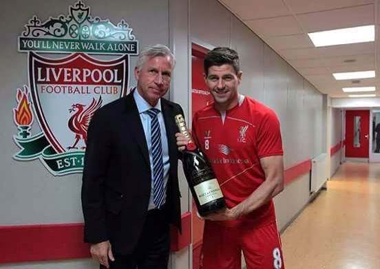 Alan Pardew presenting Steven Gerrard with a commemorative bottle of champagne before his last match at Anfield.