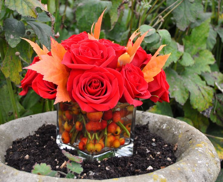 Vibrant fall arrangement of roses, fall leaves and crabapples.
