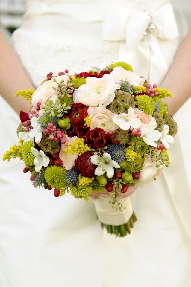 Bouquet of red ranunculus, red coxcomb, white and pink bi-colored ranunculus, green buttons, green and red hypericum berries, seeded eucalyptus, yellow goldenrod, scabiosa pods, stephanotis, pink pepperberries wrapped in ivory ribbon