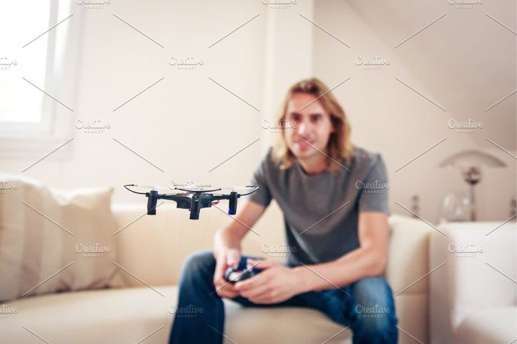 Young Man Playing With A Small Quadrocopter Drone by nullplus Photography on @creativemarket