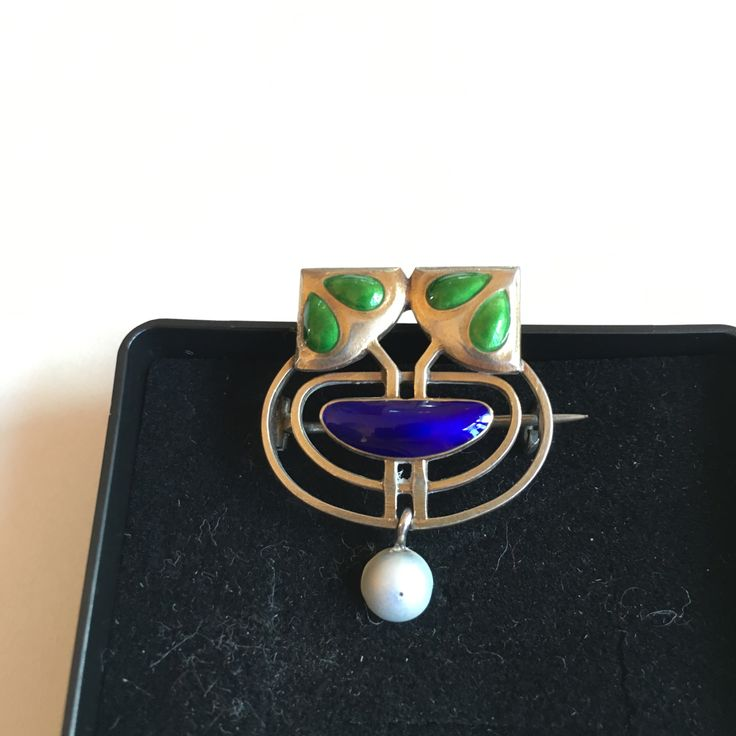 Gustav Gaudernack design for David Andersen. Silver pin-brooch in art nouveau style with blue and green enamel details and enamel half-pearl. ca. 1905