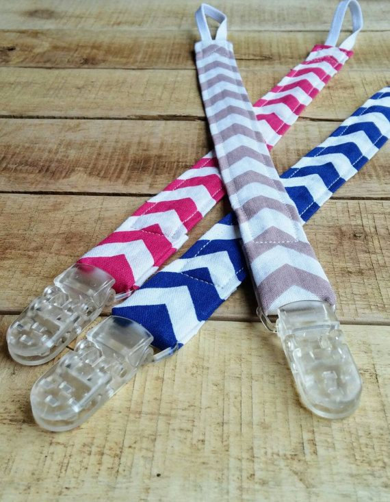 Keep your childs soother close by with this cute chevron print universal soother clip/pacifier clip. Made with 100% cotton in one of three Chevron Patterns.  It comes with an elastic on one end that loops through any soother clip or toy. On the other end it has a sturdy clip that attaches easily to clothing that cannot be removed by child. This universal soother clip is 1 wide and is 13 long. It is top stitched for durability  Makes a great toy strap as well! Easily attaches to toys to k...