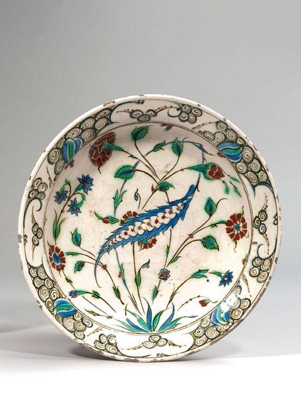 Iznik  Plat rond en céramique siliceuse à glaçure plombifère à décor bleu, rouge et vert au centre d'une palme saz, œillets et tulipe, l'aile décorée de rochers stylisés.  Début du XVIIe siècle  Diamètre : 29,2 cm