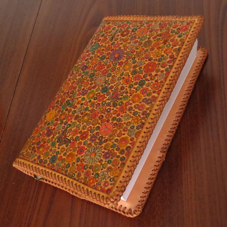 Kožený obal Z babiččiny zahrádky pro Sajla Kožený obal na knihu zdobený ražením v designu Z babiččiny zahrádky, impregnovaný, barvený. Obal je vyroben z hovězí kůže tlusté2,5mm a sešitývepřovicovým řemínkem.Uvnitř je záložka-řemínek s korálkovým přívěskem. Vnitřní klopa je zdobená monogramem. Vnitřní klopy jsou široké 10cm, takže pohodlně udrží i ...