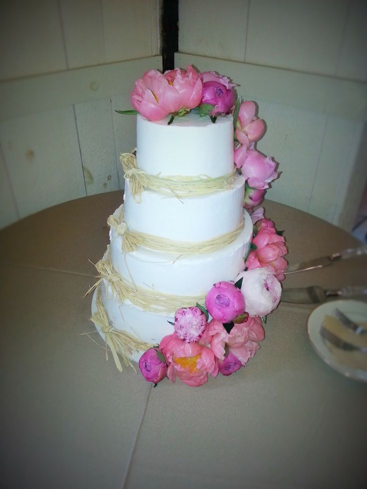 raffia wedding cake with coral and pink flowers at the