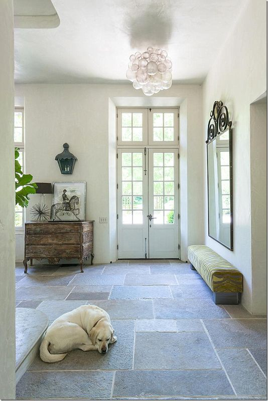 Simple country elegance. Slate entry with oversized mirror plus white walls windows with transom sand French doors.