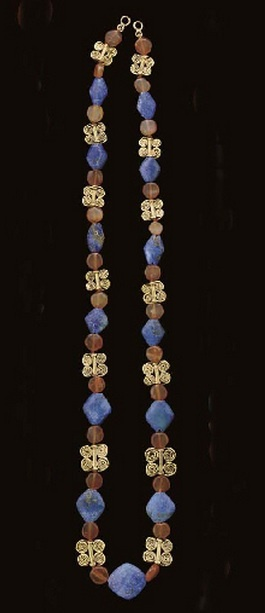 A Western Asiatic gold and Carnelian Necklace | Circa 2nd Millennium B.C. | Including fourteen gold quadruple spiral beads, each with a central tube joined to two double-spiraling wires, together with thirteen rhomboidal modern lapis lazuli beads, and twenty-six disk-shaped carnelian beads