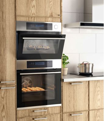 Komfyr og avtrekksvifte i rustfritt stål, i et kjøkken i eik med aluminiumsbenkeplater og håndtak.
