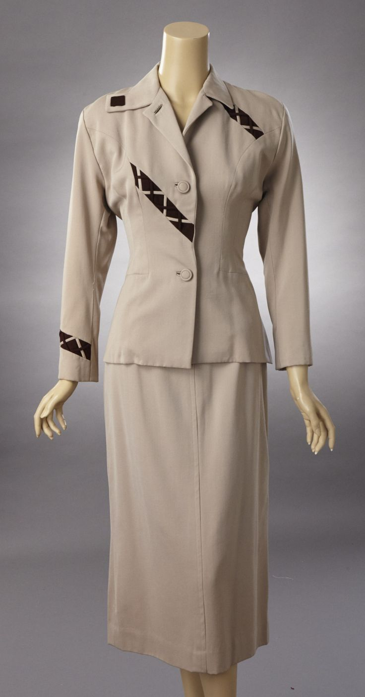 1940s Lilli Ann beige wool gabardine suit with dark brown accents. There are a few minor moth spots on the jacket. On left sleeve at elbow, right sleeve just below shoulder, The jacket is accented wit