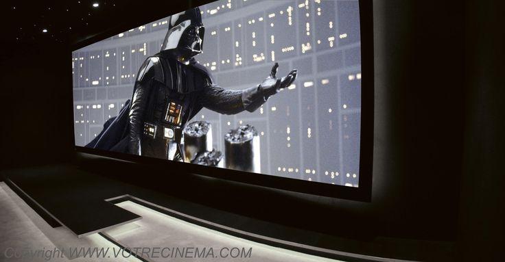 RÉALISATION D'UN HOME CINÉMA MODERNE DE 40 M2 EN ILE-DE-FRANCE L'écran est au format 2:35 cinémascope, équipé d'une toile trans-sonore compatible 4K. Le cadre est même cintré et sa courbe est rétro éclairée pour la mettre en valeur dans la salle de cinéma de luxe. Quand à l'image, elle provient d'un vidéoprojecteur 4K Ultra HD.