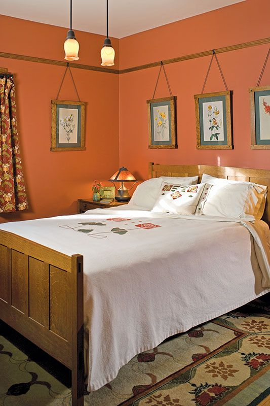 A Stickley reissued oak bed is dressed with Arts & Crafts pillows.
