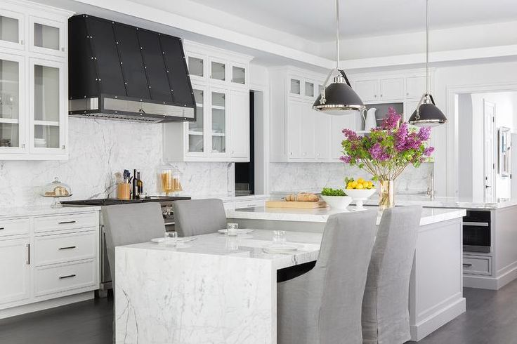 Two matching black industrial pendants hang over two identical gray matching kitchen islands topped with gray and white marble.