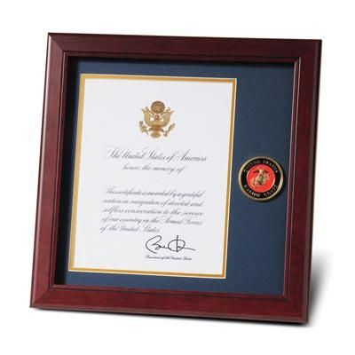 This Marine Corps Medallion Presidential Memorial Certificate Frame is designed to hold a single 8-inch x 10-inch Presidential Memorial Certificate. The certificate is set into a double layer of Marine Blue matting with Gold trim. The frame is made from Mahogany colored wood, and the outside dimensions measure 14-inch x 14-inch.