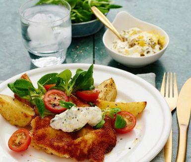Panera kycklingfiléerna i ägg, dijonsenap och ströbröd och stek dem tills de fått en gyllene och krispig yta. Servera med ugnsrostad klyftpotatis, en grönsallad med tomater och den ljuvliga kapriskrämen.