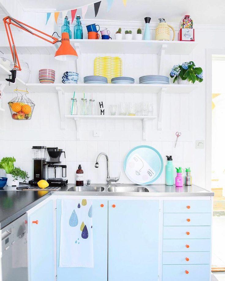 Kuchnia z błękitnymi szafkami i kolorowymi dodatkami