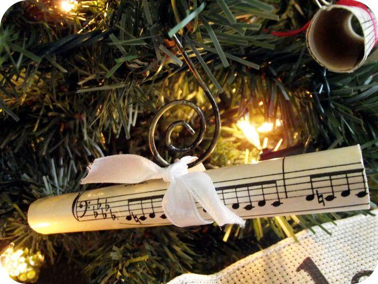 Muzyczne ozdoby bożonarodzeniowe: na zdjęciu kartka z nutami i biała wstążka na gałązce choinki