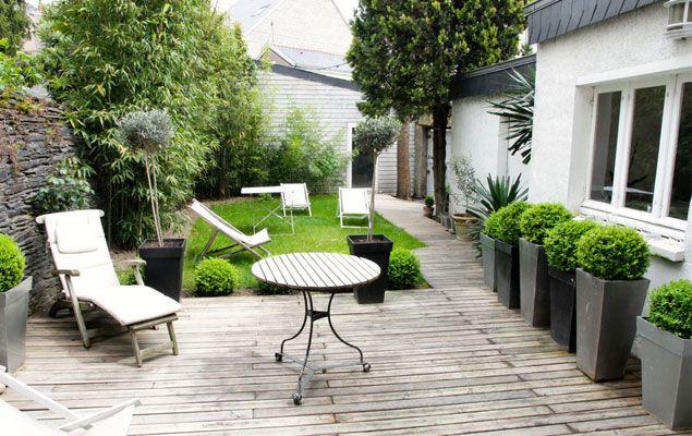 Pots dans un petit jardin avec terrasse en bois et transats.