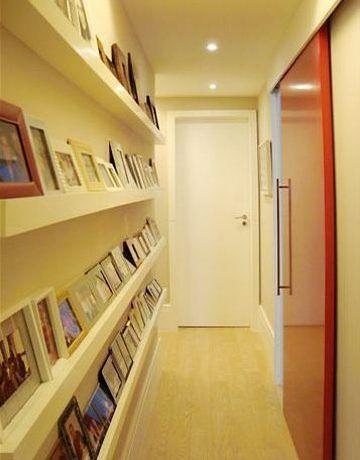 idéia para decorar o corredor com muitos porta-retratos.