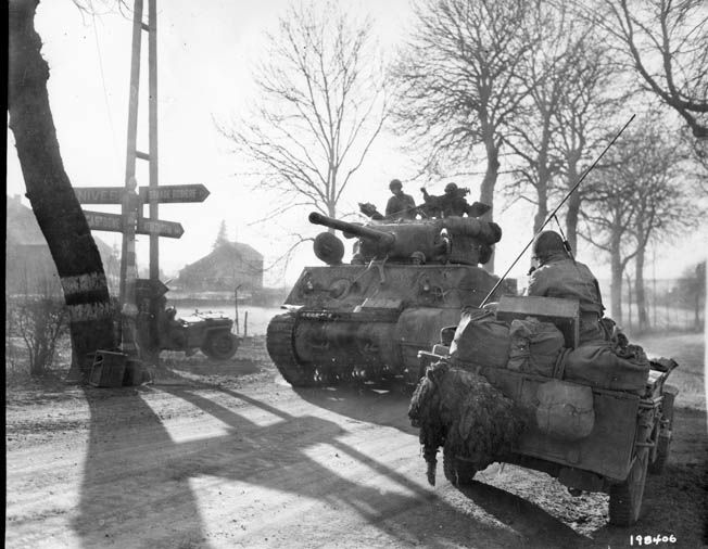 A 9th Armored Division M4 Sherman tank moves up in attempt to stem the German breakthrough, December 27, 1944.