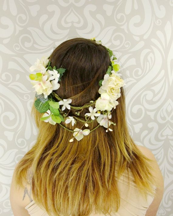 A beautiful woven vine crown decorated with a variety of green leaves and foliage, ivory and white flowers, buds and berries. This beautiful