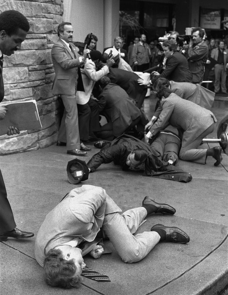 March 30, 1981 — Assassination attempt on President Reagan. Secret Service agent Timothy J. McCarthy, Washington police officer Thomas K. Delahanty, and presidential press secretary James Brady lie wounded on the street after shots were fired at President Reagan on March 30, 1981. McCarthy threw himself into the line of fire after gunman John Hinckley Jr. had fired six shots from a crowd.