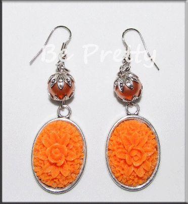 Brincos com pérolas laranja e medalhões com flor laranja.