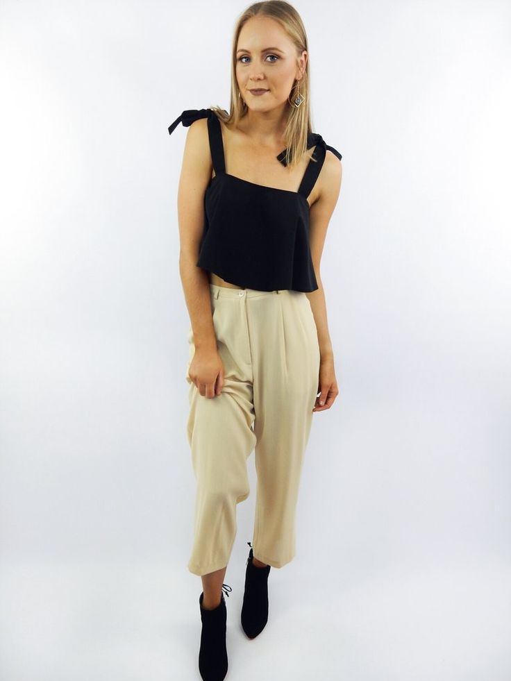 The Funk Yellow Trousers feature pleats, high waist, wide leg, belt loops, and pockets at sides. Trousers have been pinned on Bec to show correct fit.