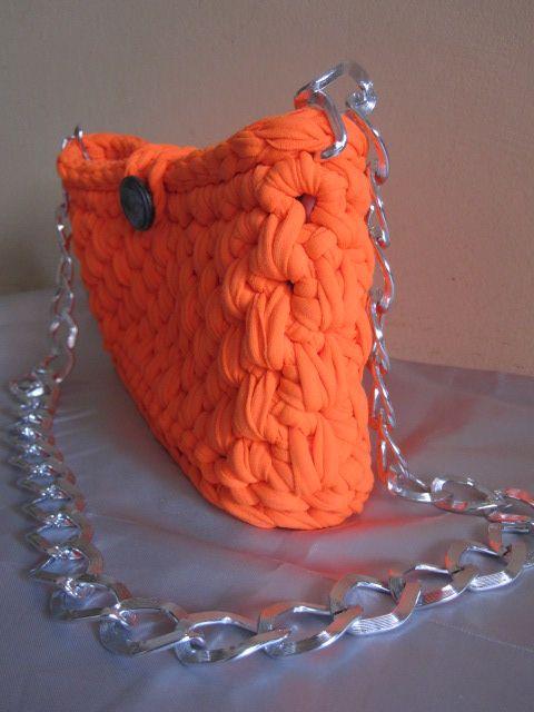"""""""Orange Bag"""" Borsa in fettuccia con fondo piatto. Bottone e catena color argento. Foderata. Misure: 26x13x7cm; catena 85cm."""