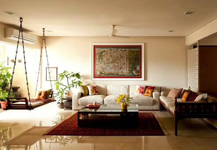 A drawing room having Indian look with swing, paintings and colourful cushions representing traditional Indian style