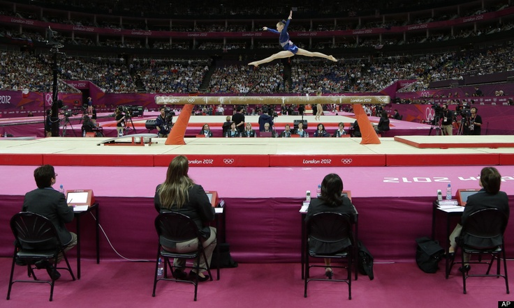 Judges watch gymnast Rebecca Tunney from Britain perform on the balance beam during the artistic gymnastics women's individual all-around competition at the 2012 Summer Olympics, Thursday, Aug. 2, 2012, in London.