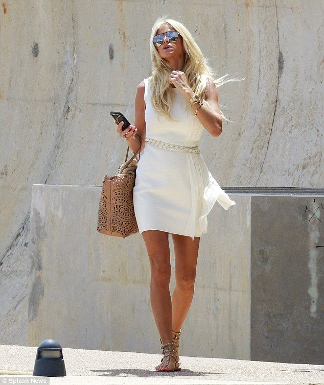 Looking all-white! The 41-year-old poured her curves into a flattering white mini dress that cinched in her tiny waist with delicate gold detailing